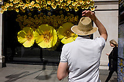 Man in straw hat in front of Apple Watch window display in Selfridges, central London.