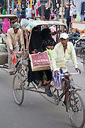 Muslim women travel by rickshaw in crowded street scene in city of Varanasi, Benares, Northern India