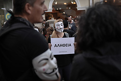 November 3, 2018 - Athens, Greece - A participant seen standing wearing anonymous masks while holding a placard during the protest..Anonymous is a vegan activists group wearing black clothes while holding laptops and placards as they demonstrate against exploitation of animals, The Cube of Truth is a peaceful static demonstration akin to an art performance. (Credit Image: © Nikolas Joao Kokovlis/SOPA Images via ZUMA Wire)