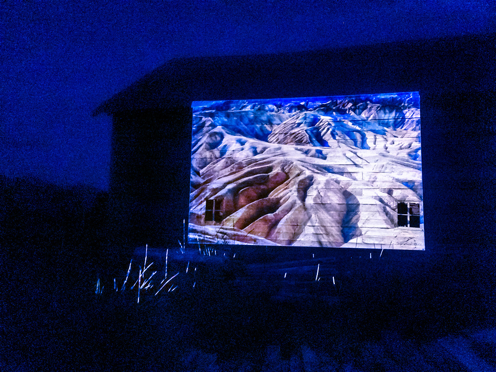 Phototaxis projector test with image by Sherly Hester on side of Nik Tavenner's barn