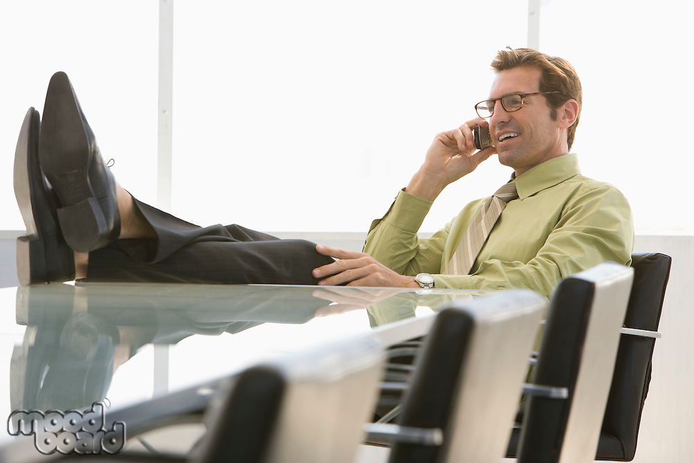 Business man using mobile phone in conference room