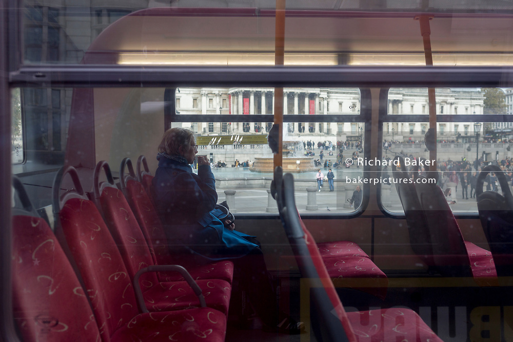 A single female sits in a rear seat of a London bus, as it drives past Trafalgar Square, on 28th October 2019, in Westminster, London, England.
