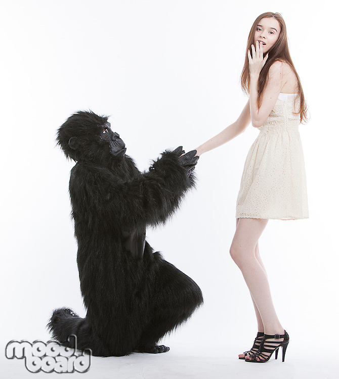 Man in gorilla costume proposing surprised young woman against white background