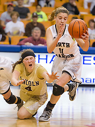 North Marion guard Christa Tobin (11) and Lincoln guard Hope Bray (4) dive for a loose ball at half court during a first round game at the Charleston Civic Center.