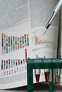 DNA samples in a test tube rack with graphics charts reference in the background