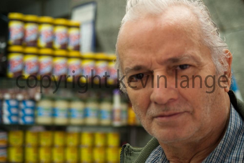 a haggard senior man portrait at a cafe stand in copacabana, rio de janeiro, brazil.