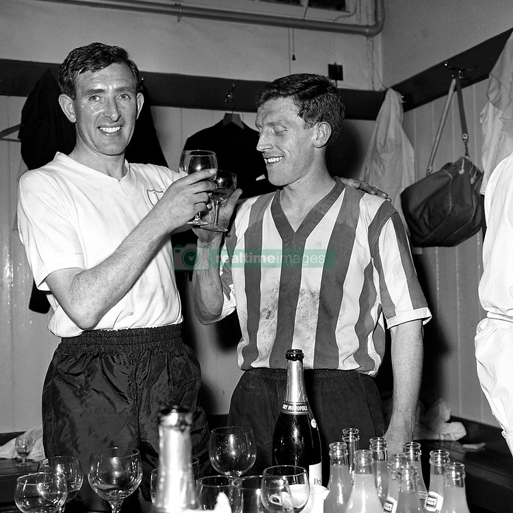 Danny Blanchflower, captain of Tottenham Hotspur, and Tony Kay (striped shirt), captain of Sheffield Wednesday, toast each other with champagne in the dressing room after Tottenham Hotspur had beaten Sheffield Wednesday 2-0.