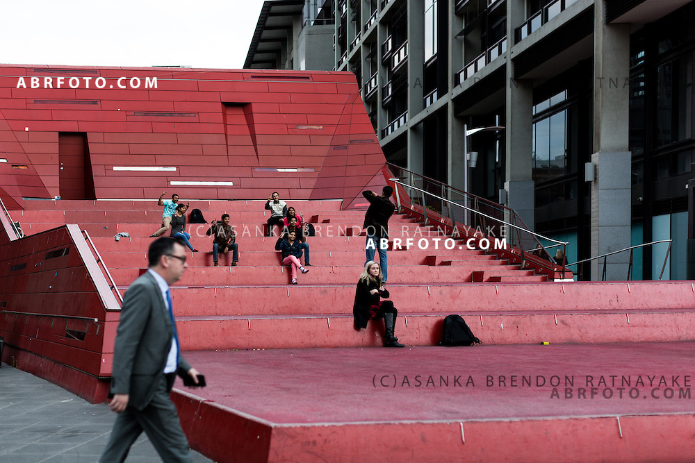 People sit and pose for a photo on the red post modern amphitheatre at as pedestrians walk & ride by at Queensbridge Square Melbourne Victoria Australia
