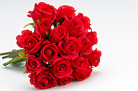 Bouquet of artificial red roses, isolated, space for copy in the side.