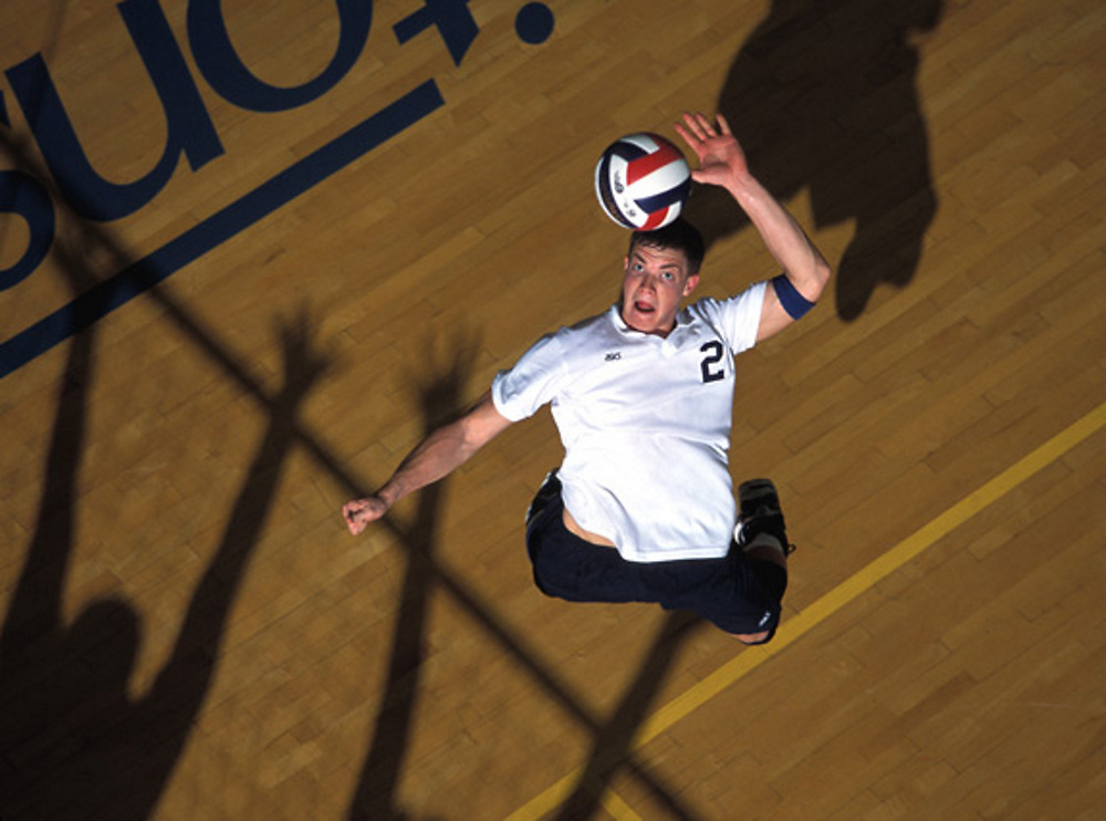 San Diego, CA - September, 2002 - Jim Waller from University of California San Diego, arches backwards to hit the ball in a game against Pepperdine University. Ghostly shadows of blockers seem the only obstacle to yet another successful hit . Photo by Wally Nell - VOLLEYBALL magazine.