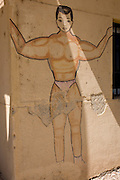 A detail of a mural showing the macho physique of a bodybuilder, on the wall outside a community gym in the village of Gezirat on the West Bank of Luxor, Nile Valley, Egypt.