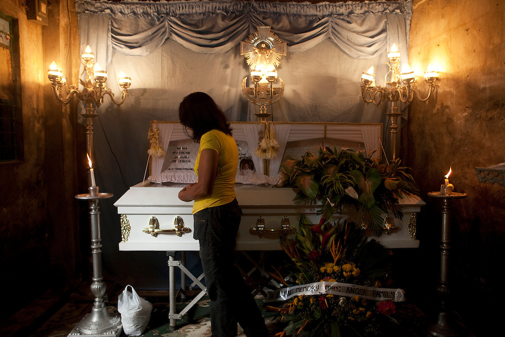 Priscilla Amalin at her husband Generoso's coffin on the day of his funeral. Generoso Amalin died age 57. He had a weak heart, hyper tension and kidney stones. Manila, Philippines.