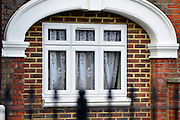 © Licensed to London News Pictures. 08/04/2013. London, UK Net curtains are pulled back at the North Korean Embassy in Ealing in West London today, 8th April 2013. The Embassy is based in a 1920's detached house in a residential area. Tensions are high between countries around the world and the North Koreans. Photo credit : Stephen Simpson/LNP