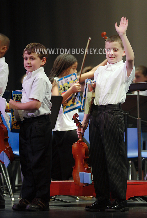 Middletown, NY - An elementary school student waves to his family after a band concert on the stage at Middletown High School on May 28, 2008.