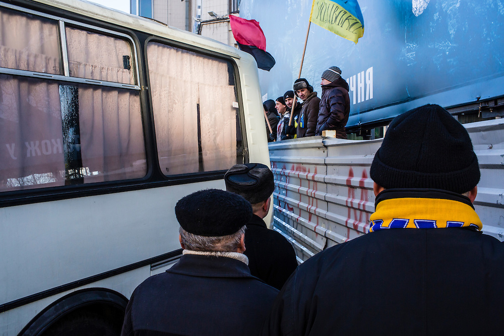 KIEV, UKRAINE - DECEMBER 14: Anti-government protesters stand near buses used by police to separate them from a pro-government rally on December 14, 2013 in Kiev, Ukraine. Thousands of people have been protesting against the government since a decision by Ukrainian president Viktor Yanukovych to suspend a trade and partnership agreement with the European Union in favor of incentives from Russia. (Photo by Brendan Hoffman/Getty Images) *** Local Caption ***