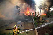 May 15, 2014 - Escondido, California, U.S -<br /> <br /> California Wildfires 2014 - Cocos Fire<br /> <br />  Escondido Fire Department firefighter Dominic Polito sprays water on a home to prevent it from catching fire near a house on fire near Country Club Drive in Harmony Grove Thursday afternoon.<br /> ©Exclusivepix