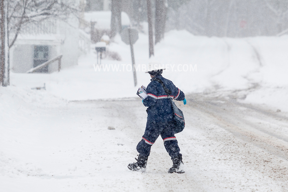 Middletown, New York - A mail carrier carefully crosses the street during a snowstorm on Feb. 9, 2017.