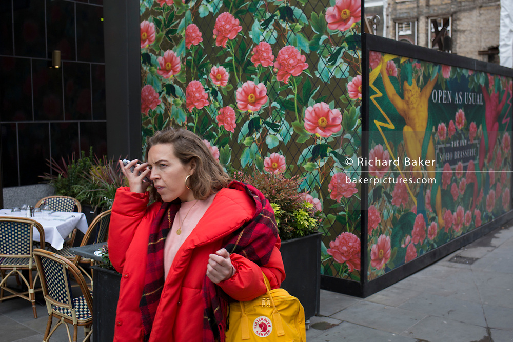 A parting hug from friends and the temporary construction hoarding in Broadwick Street, Soho, on 5th March 2019, in London, England.
