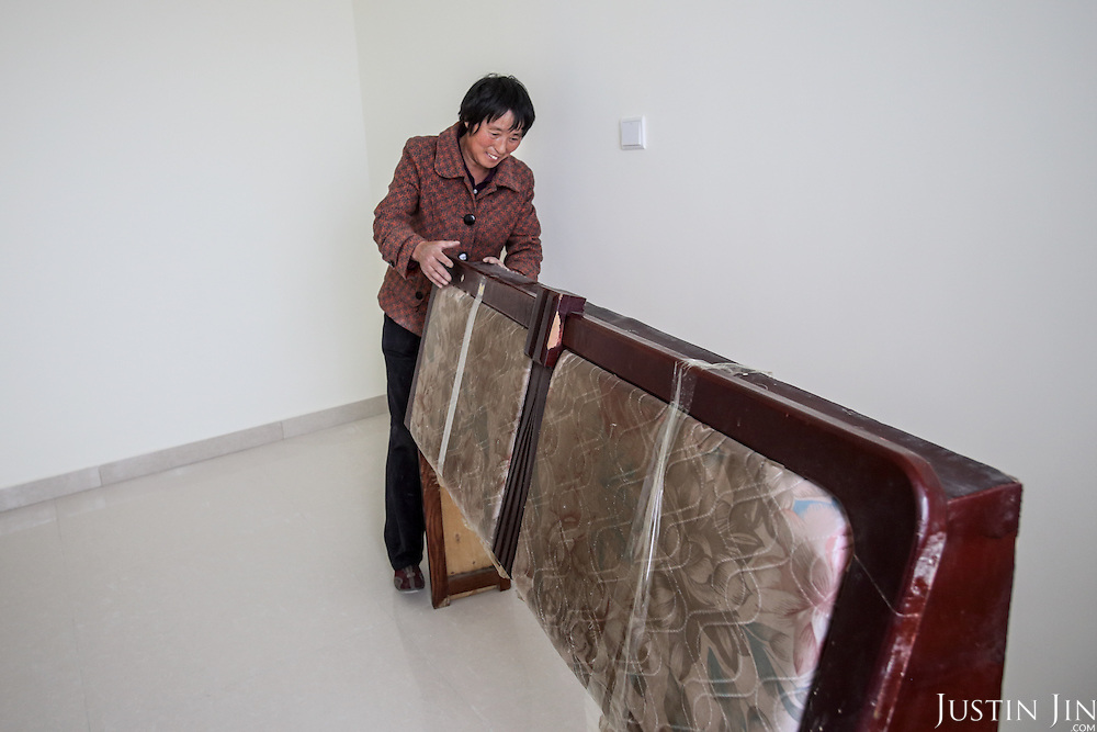 Chen Hua, 50, moves into her new urban home in Liaocheng city in the northeastern Chinese province of Shangdong.<br /> <br /> Her former village house was bulldozed by the government three years ago to make way for high-rise development. <br /> <br /> In the four years between her rural home being razed and the completion of her new city apartment, she and her family lived in temporary village housing such as this one. <br /> <br /> China is pushing ahead with a dramatic, history-making plan to move 100 million rural residents into towns and cities between 2014 and 2020 &mdash; but without a clear idea of how to pay for the gargantuan undertaking or whether the farmers involved want to move.<br />