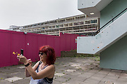 London, England, UK, May 31 2018- Housing activist and local resident Aysen Dennis takes pictures of a block currently almost empty of Aylesbury Estate,  a housing estate in Walworth, South East London. <br /> Aylesbury  estate, once the largest estate in Europe, is currently undergoing a major regeneration programme by demolishing and replacing of the dwellings with modern houses controlled by a housing association. Some residents and activists including Ms Dennis still protest against the demolition and the gentrification of London.<br /> London is facing a major housing crisis, due to rising cost and under-supply.