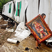 "A young resident carries a painting of Santa Muerte from his family's wrecked trailer in the aftermath of a flood resulting from Tropical Storm, Lee, in Woodbridge, VA, on September 9, 2011.  Santa Muerte, or ""Saint Death"", is a venerated figure in Mexican culture and often is associated with the granting of favors or protection.  Miraculously, there were no deaths or serious injuries as a result of the otherwise devastating flood which left dozens of families homeless. For The News & Messenger (Manassas, VA)."