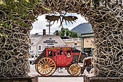 A tourists stagecoach the Elk Antler Arch in George Washington Memorial Park, known as the Town Square in Jackson Hole, Wyoming. The Town Square's four arches are built entirely from local elk antlers. Each arch is supported by a steel framework and constructed by hand using more than 2,000 antlers each. The arches are held together mostly by friction and gravity and need to be rebuilt about every 50 years.