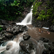 People cool off in the waters below La Mina Falls in Puerto Rico's El Yunque National Forest.  The park contains 24 miles of recreational trails and is maintained by the National Park Service.