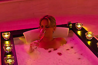 A woman relaxing in a bath tub with rose pedals, Futeresse suite in the spa, Brenner's Park Hotel & Spa, Baden Baden, Baden-Württemberg, Germany