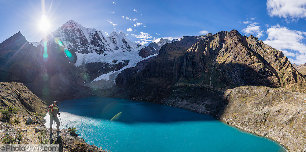 A hiker admires turquoise Solteracocha lake (4120 m) under glaciers of Nevado Jirishanca (Icy Beak of the Hummingbird, 6126 m or 20,098 feet). Day 9 of 9 days trekking around the Cordillera Huayhuash in the Andes Mountains, near Llamac, Peru, South America. This panorama was stitched from 5 overlapping photos.