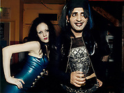 Young goth woman and man standing together at pub.