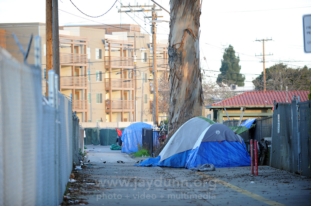 New affordable housing looms behind tents of the homeless in an alley off Market Way in Salinas.