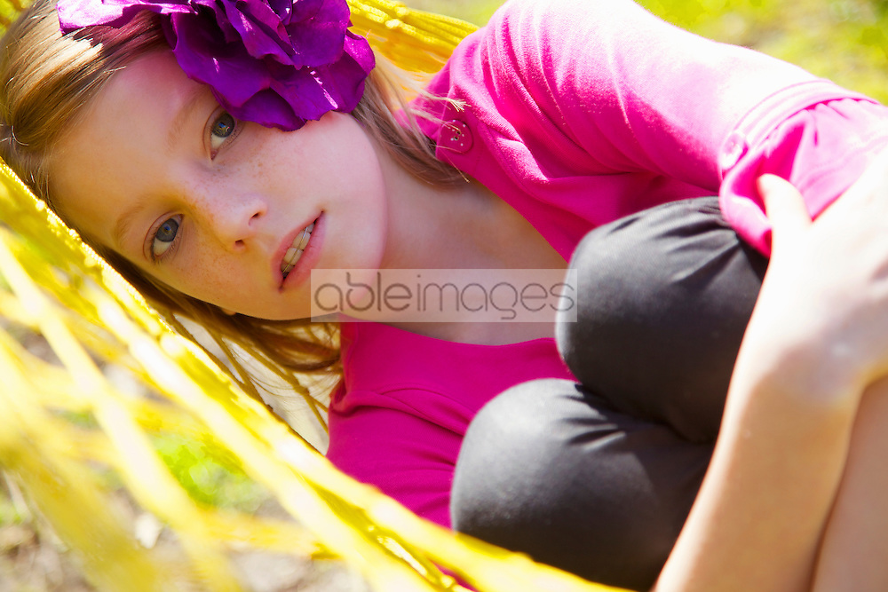 Close up of a girl lying on a hammock hugging her knees