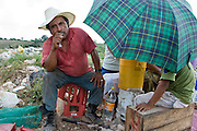 09 NOVEMBER 2004 - TAPACHULA, CHIAPAS, MEXICO: Daniel Ramirez Lopez, a garbage buyer, waits for garbage pickers to bring him things they found in the garbage in the municipal garbage dump in Tapachula, Chiapas, Mexico. About 130 people, the poorest of the poor in Tapachula, work in the dump picking through the garbage hoping to find tidbits they can use or sell to brokers who sit on the edge of the dump and resell the garbage. Most of the dump workers are Guatemalan migrants who crossed the border hoping, at one time, to get to the United States. Now they have settled for an existence on the very edge of Mexican society. PHOTO BY JACK KURTZ