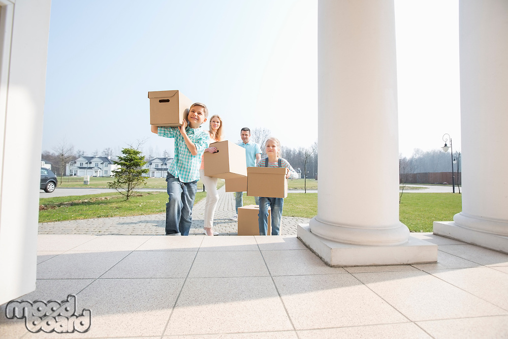 Family with cardboard boxes entering into new house