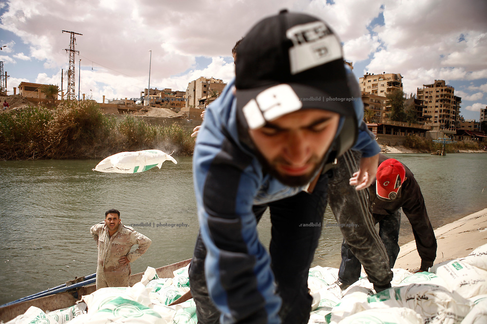 Volunteers of local relief organisation Rawafed transport 5 tons of wheat flower by boat across a sidearm of the Eurphrates river. It is the only supply line to get flower to bakeries in Deir az-Zor. All residents depend on this commitment. Residents of eastern syrian town Deir az-Zor joined arab spring protests against the regime of Bashar al-Assad from its early beginning in March 2011. Since summer 2012 the town with few hundred thousand inhabitants is embattled between the Syrian Army and different opposing rebel groups like Free Syrian Army and Jabhat al-Nusra. Deir az-Zor is target to constant shelling by artillery, war planes and short range missiles. Almost 70 percent of the town is rebel held while government forces remain in control over some residental areas and a strategic important airport. Deir az-Zor is widely damaged and some areas almost totally destroyed by fierce and long lasting battles. All direct road connections to Deir az-Zor are cut and fighters and returning residents as well depend on one provisional supply line across the Euphrates river which is regularly targeted by government snipers.