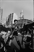 """Beirut, Lebanon June 1982. A group of Shiite militiamen of the Amal movement, patroling West-Beirut main avenue on an armed vehicle at the begining of the israeli military operation """"Peace in gallile"""" against PLO. ©Herve Merliac"""
