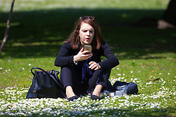 A woman enjoys her lunch break on a perfect spring day in Regents Park. London, May 04 2018.