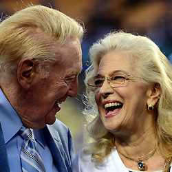 Los Angeles Dodgers broadcaster Vin Scully, left, shares a moment with his wife Sandra as he was honored by the Guinness World Records for the longest career as a sports broadcaster for a single team on his bobble head night prior to a Major League Baseball game between the Arizona Diamondbacks and the Los Angeles Dodgers on Wednesday, Sept. 23, 2015 in Los Angeles.