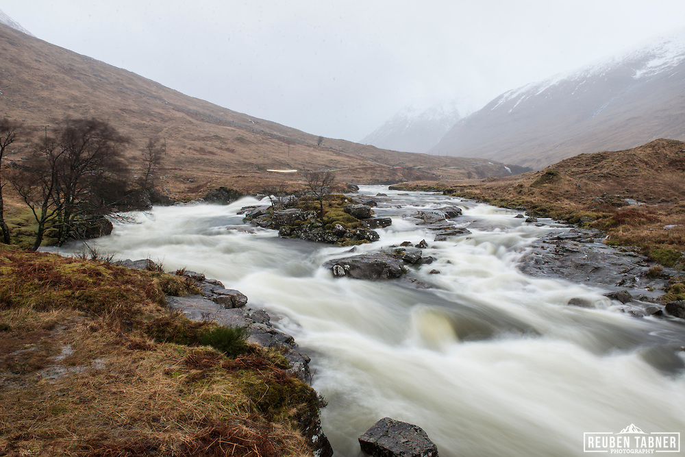 A river in full spate flows down the hill side in Glen Etiv, in the Highlands of Scotland.