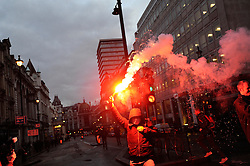 © Licensed to London News Pictures. 30/11/2011. LONDON, UK. Protester holds up a flare before Occupy LSX and activists attempt to occupy Panton House in Panton Street after the November 30 Public Sector march in London. Photo credit : Peter Webb/LNP