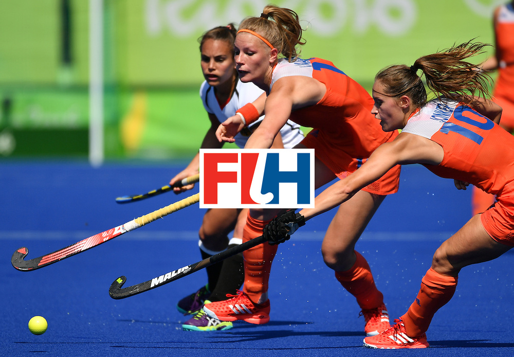 Germany's Lisa Altenburg (L) vies with Netherlands' Caia van Maasakker (C) and Netherlands' Kelly Jonker during the women's semifinal field hockey Netherlands vs Germany match of the Rio 2016 Olympics Games at the Olympic Hockey Centre in Rio de Janeiro on August 17, 2016. / AFP / Pascal GUYOT        (Photo credit should read PASCAL GUYOT/AFP/Getty Images)