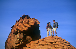 two men standing together on a rock formation in Nevada
