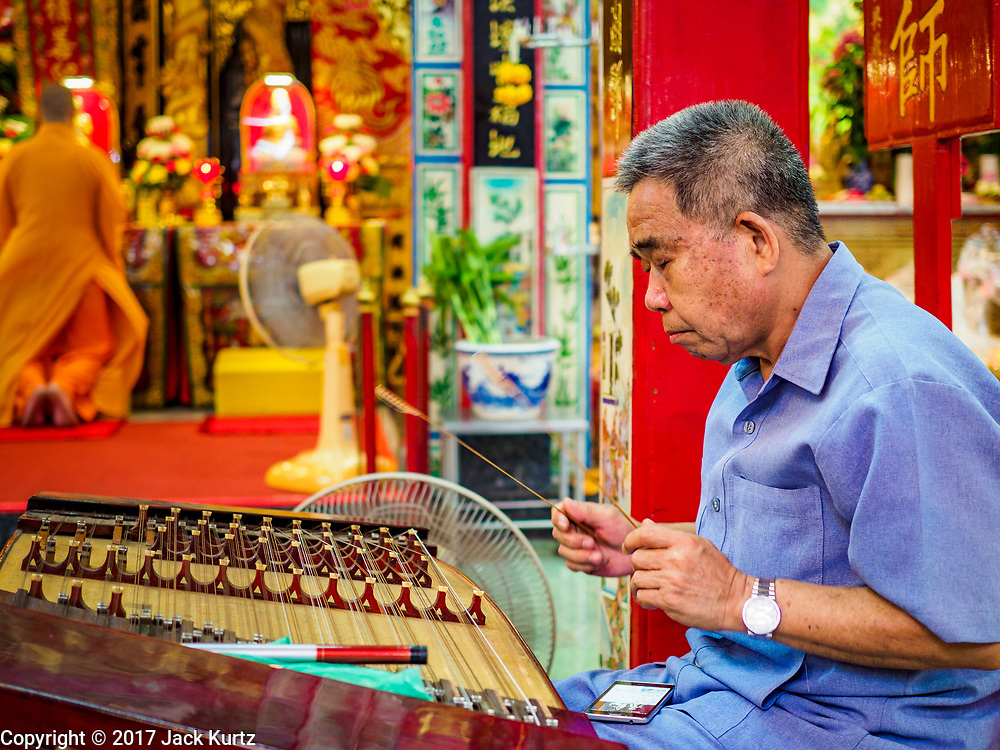 """22 AUGUST 2017 - BANGKOK, THAILAND: A traditional Chinese musician performs during a ceremony on the first day of Hungry Ghost Month at the Poh Teck Tung Shrine in Bangkok's Chinatown. The seventh lunar month (August - September) is when many Chinese believe Hell's gate will open to allow spirits to roam freely in the human world. Many households and temples hold prayer ceremonies throughout the month-long Hungry Ghost Festival (Phor Thor) to appease the spirits. During the festival, believers will also worship the Tai Su Yeah (King of Hades) in the form of paper effigies which will be """"sent back"""" to hell after the effigies are burnt.      PHOTO BY JACK KURTZ"""