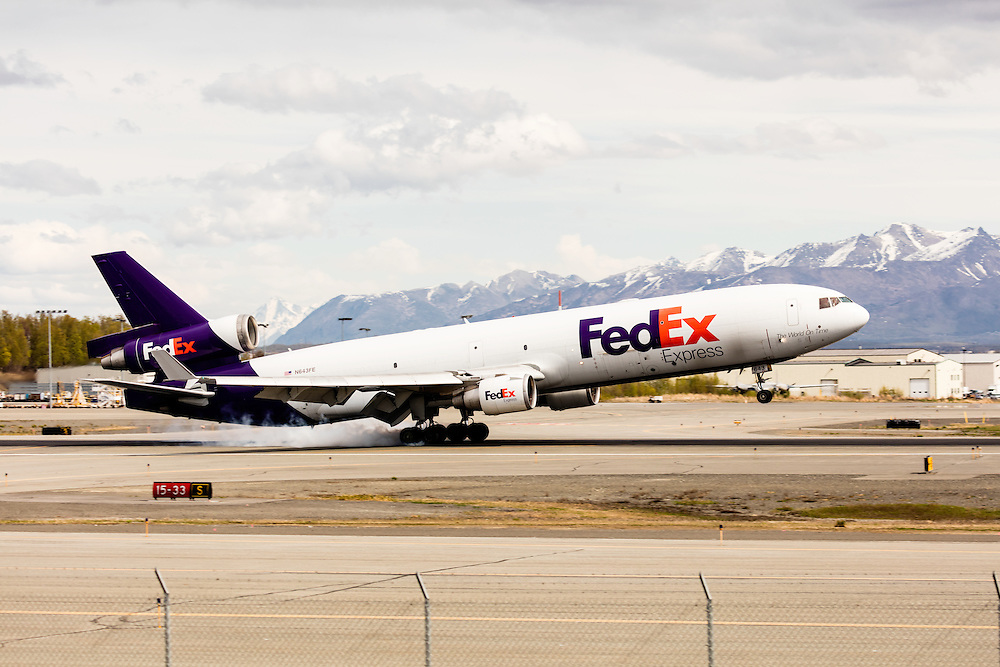 FedEx cargo jet landing at Ted Stevens Anchorage International Airport in Southcentral Alaska with the Chugach Mountains in the background. Spring. Afternoon.