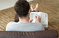 Young man sitting on sofa doing crossword puzzle in newspaper back view