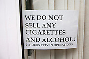 """Window sign stating: Wed no not sell any cigarettes and alcohol! 24 hours CCTV in operation""""."""