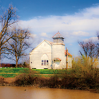 The solid wood church stands in midst of cotton trailers tractors and fields on the banks of the Deer Creek River.