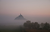Mont St. Michel emerging from the dawn mists as if from another world.