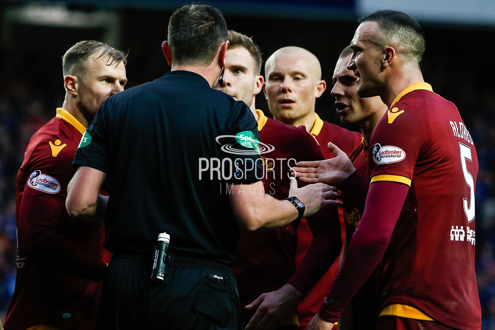 Motherwell players surround referee Craig Thomson following the red card and penalty decision during the Ladbrokes Scottish Premiership match between Rangers and Motherwell at Ibrox, Glasgow, Scotland on Sunday 11th November 2018.