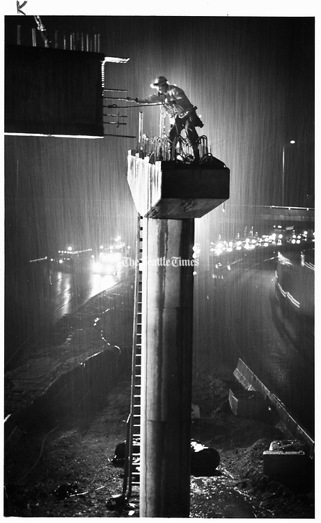 A journeyman guides a steel girder into place on a future ramp connecting Interstate 405 south to Highway 520 east. (Teresa Tamura / The Seattle Times, 1993)